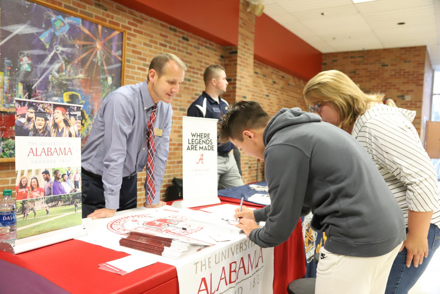 At the University of Alabama table, Ethan Lee (11) fills out his contact information so the school can talk to him again about future plans. Many colleges and universities met many with Brighton area students on College Night.