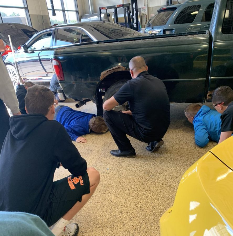 ASE Master Certified teacher Robert Delaney works with students in the auto tech lab.