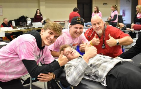 Seniors Liam Fay, TJ Richards and one of the Red Cross nurses support Paul Skoczylas as he donates blood at the Drive. Throughout the day, students came by the Aux Gym for their chance to help others by donating their blood.