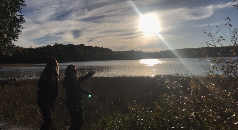 Seniors+Madeline+Wiktorowski+and+Josie+Nicita+hanging+out+at+the+lake+before+a+football+game.+Off+of+Cunningham+Lake+Rd%2C+this+lake+has+the+best+sunsets.+Photographer+Heather+Goulette+%2811%29+did+a+great+job+of+capturing+the+sun%E2%80%99s+reflection+on+the+lake.+