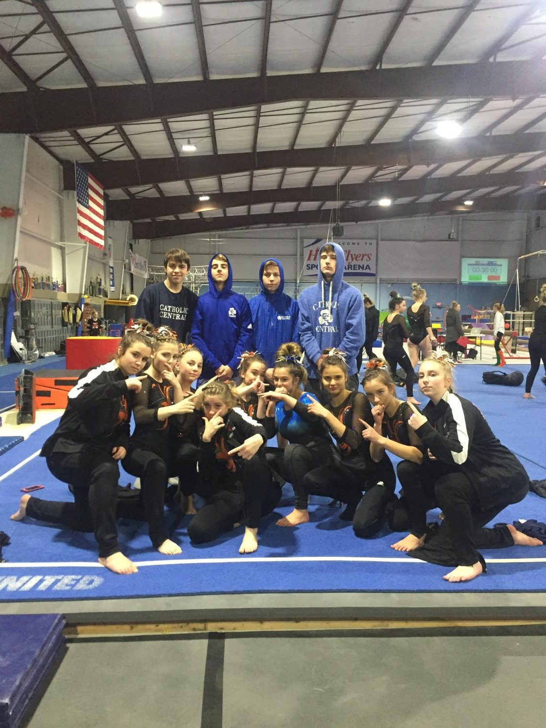 The+gymnastics+take+a+picture+with+their+Catholic+Central+supporters%2C+holding+up+one+finger+to+celebrate+their+win+against+Livonia+Churchill.+%E2%80%9CIt+was+really+funny%2C%E2%80%9D+Libby+Stafford+%2810%29+said.+%E2%80%9CI+don%E2%80%99t+even+know+who+they+were+here+to+watch.%E2%80%9D